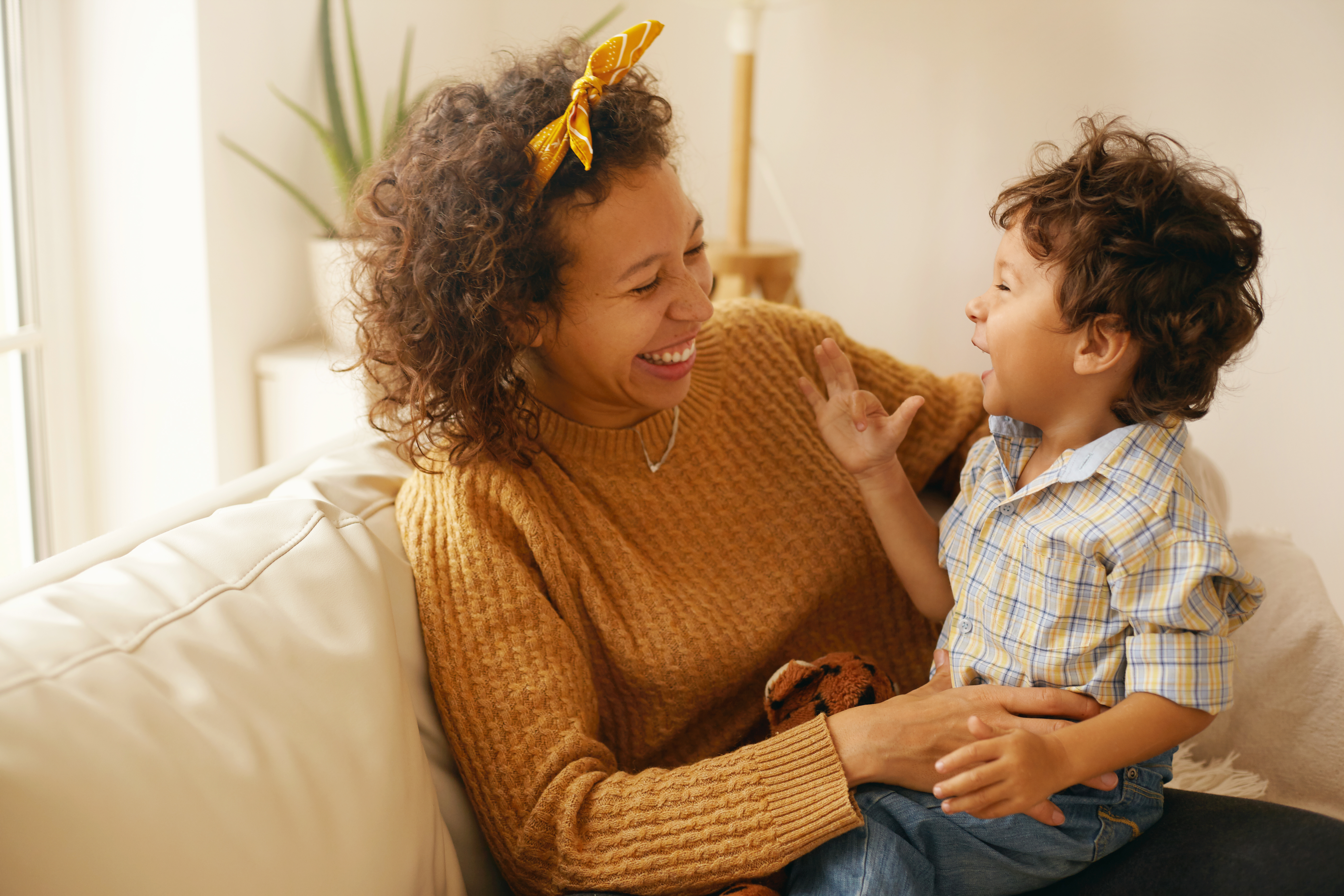 indoor-shot-of-happy-young-hispanic-woman-with-brown-wavy-hair-relaxing-at-home-embracing-her-adorable-toddler-son-cheerful-mother-bonding-with-infant-son-sitting-on-sofa-in-living-room-laughing